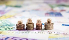 Слово Geld на стогах монетки, предпосылке наличных денег Стоковые Изображения RF