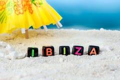 Слово Ibiza сделано пестротканых писем на снег-белом песке против голубого моря Стоковая Фотография RF