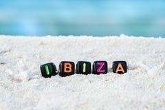 Слово Ibiza сделано пестротканых писем на снег-белом песке против голубого моря Стоковое фото RF