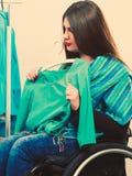 С ограниченными возможностями девушка на кресло-коляске выбирая одежды Стоковое Фото