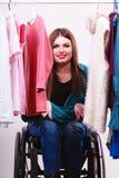 С ограниченными возможностями девушка на кресло-коляске выбирая одежды Стоковое Изображение