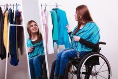С ограниченными возможностями девушка на кресло-коляске выбирая одежды Стоковая Фотография RF