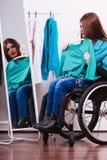 С ограниченными возможностями девушка на кресло-коляске выбирая одежды Стоковая Фотография