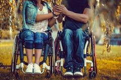 С ограниченными возможностями молодые пары на 2 кресло-колясках Стоковое Изображение