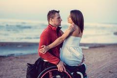 С ограниченными возможностями пары отдыхая на пляже Стоковые Фото