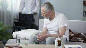 С ограниченными возможностями человек сидя на софе на доме престарелых, мужская медсестра принося кресло-коляску Стоковое Изображение