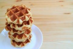 Сложенные вверх бельгийские Waffles на белой плите служили на деревянном столе, с открытым космосом для текста Стоковая Фотография