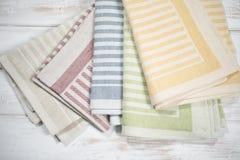 Сложенные салфетки таблицы с сплетенными дизайнами нашивки различных цветов Стоковые Фотографии RF