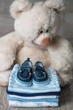 Сложенный голубой и белый bodysuit с ботинками на ем около предпосылки большого плюшевого медвежонка серой деревянной пеленка для Стоковое Изображение RF