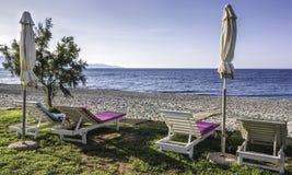 Сложенный парасоль с sunbeds на пустом пляже Стоковая Фотография