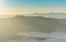 Слой горы в луче восхода солнца утра и зима fog Стоковые Фотографии RF