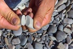 Сломайте в половине камня поглотил в пальцах руки человека Стоковые Фото