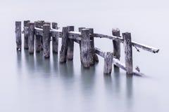 Сломанный вниз с старых столбов пристани в спокойной воде, покрытой с светлым dus Стоковое фото RF