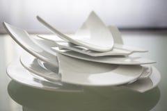 Сломленные белые плиты на стеклянном столе Стоковое Изображение RF
