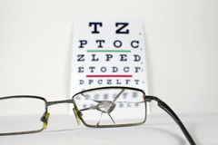 Сломленные зрелища на диаграмме испытания глаза Snellen Opticians стоковые фотографии rf