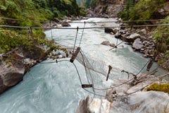 Сломленный висячий мост в Гималаях Непале Стоковая Фотография