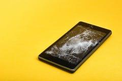 Сломленный мобильный телефон на желтом цвете Стоковые Изображения