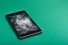 Сломленный мобильный телефон на зеленом цвете Стоковые Изображения