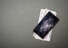 Сломленный мобильный телефон с деньгами на зеленом цвете Стоковые Изображения