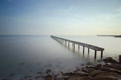 Сломленный мост и волны разбивая на море на во время заходе солнца Стоковое Изображение