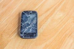 Сломленный телефон на деревянной таблице , телефон повреждения с селективным фокусом Стоковое фото RF