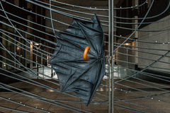 Сломленный дунутый ветер повредил зонтик на загородке Стоковое Изображение