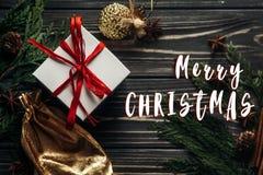 С Рождеством Христовым знак текста на настоящих моментах с красной лентой и золотой Стоковые Фотографии RF
