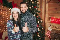 С Рождеством Христовым и с новым годом Молодые пары празднуя праздник дома 2 счастливых болезненного и женщины держа их Стоковое Фото
