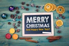 С Рождеством Христовым и с новым годом предпосылка красит желтый цвет праздника красный Орнаменты и оформление на деревянном стол Стоковая Фотография