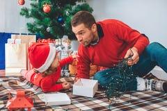 С Рождеством Христовым и с новым годом Славное изображение родителя и ребенка на одеяле Девушка лежит на животе Взгляд человека н стоковая фотография