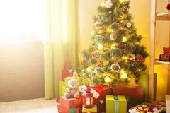 С Рождеством Христовым и счастливые праздники! Красивая живущая комната украшенная для рождества Настоящие моменты и подарки под  стоковая фотография