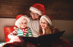 С Рождеством Христовым! отец семьи читает к книге детей перед кроватью стоковое изображение