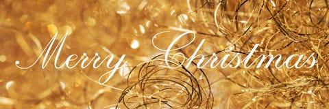 С Рождеством Христовым, помечающ буквами на золотой предпосылке стоковое фото