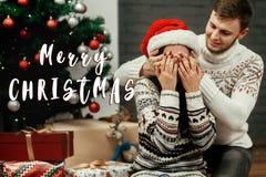 С Рождеством Христовым приветствие знака текста с счастливыми парами семьи, Ханом Стоковое фото RF