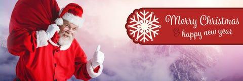 С Рождеством Христовым счастливый текст и Санта Клаус Нового Года в зиме с мешком стоковое фото rf