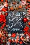 С Рождеством Христовым литерность на темной доске и различное красное украшение праздника на темной деревенской предпосылке, взгл Стоковое Изображение