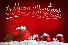 С Рождеством Христовым шарики концепции в снеге, приветствуя стоковое фото