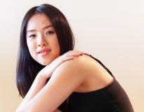 С слабыми улыбкой и рукой на чуть-чуть взглядах молодой женщины плеча к камере Стоковое Изображение RF