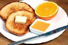 Служат завтрак: здравицы с вареньем, маслом и апельсином Стоковые Изображения