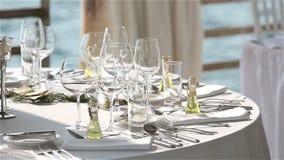 Служат таблица в ресторане на пляже в Европе на заходе солнца видеоматериал