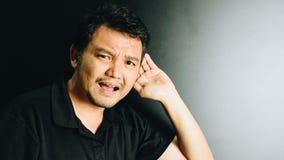 Слух человека Азии глухой для слушать в темном стиле стоковые фото