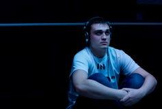 Слушать молодого человека сидя к музыке стоковая фотография rf