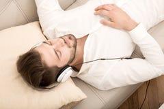 Слушая музыка на софе Стоковое Изображение RF