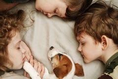 ?hildren che pone e che abbraccia un cucciolo fotografia stock