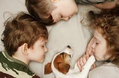 ?hildren che pone e che abbraccia un cucciolo fotografie stock libere da diritti