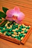 Сinnamon棍子,胶囊,片剂,在木头的一朵兰花花 免版税库存图片