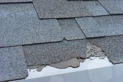 Ð¡loseup view of asphalt shingles roof damage that needs repair. Ð¡loseup view of asphalt shingles roof damage that needs repair stock image