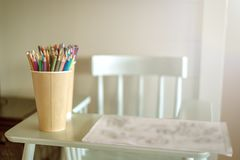 Сolored pencils are on the high chair. stock photos