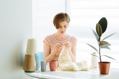 Ð¡raftswoman knitting dress with crochet in cozy workplace at home interior. Female working with tender lace. Business handmade stock photo