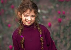 Ð¡ute girl in a crimson turtleneck and with two pigtails stock photo